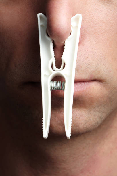 Man with Clothes Pin on Nose Close Up stock photo