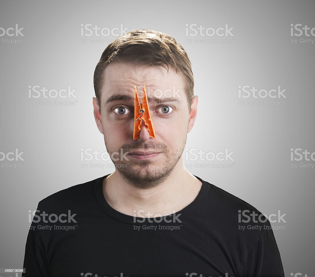 Man with clothespin on his nose. stock photo