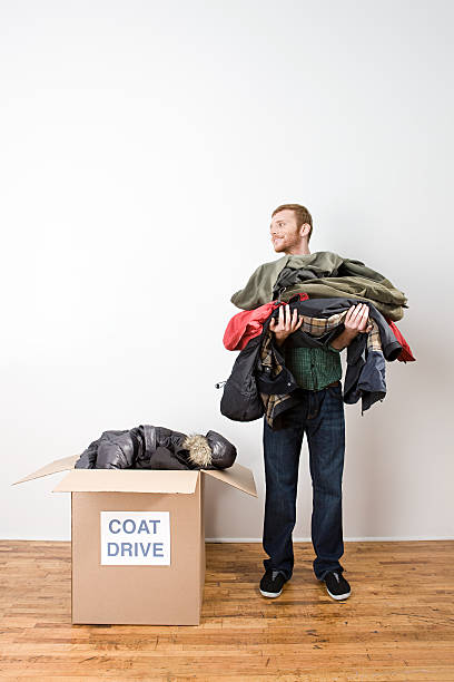 Man with coats for coat drive  clothes in box stock pictures, royalty-free photos & images