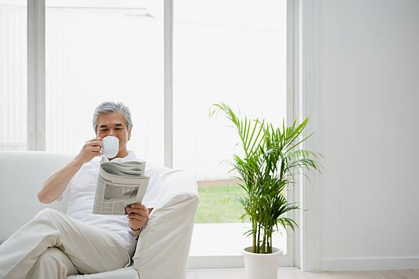 Man with coffee and a newspaper stock photo