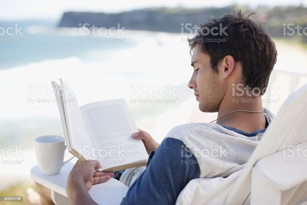Man with coffee cup reading book in deck chair overlooking ocean stock photo