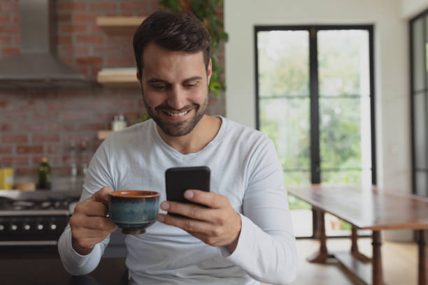 Man with coffee cup using mobile phone stock photo