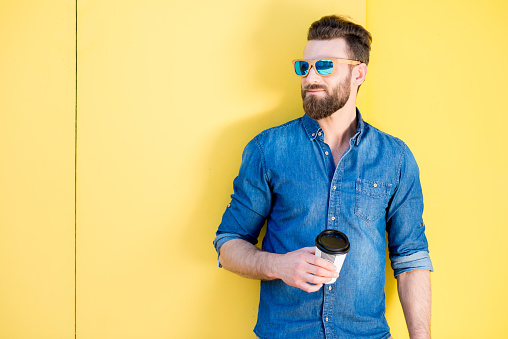 Man with coffee on the yellow background