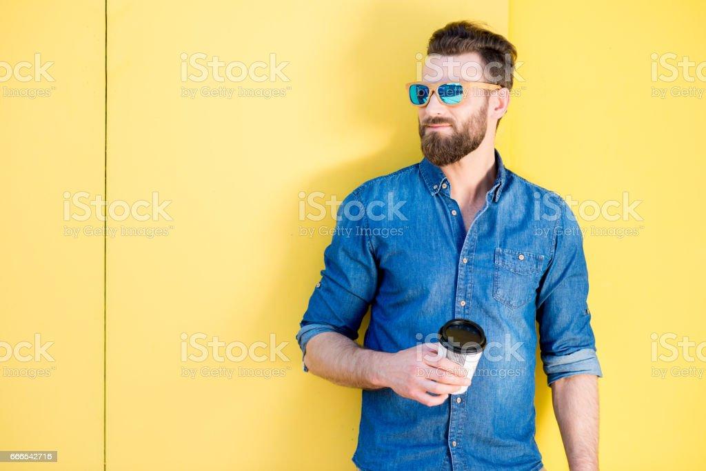 黄色の背景にコーヒーを持つ男 ストックフォト