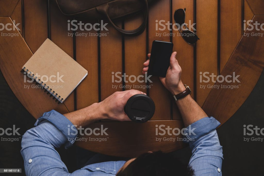 man with coffee to go using smartphone stock photo