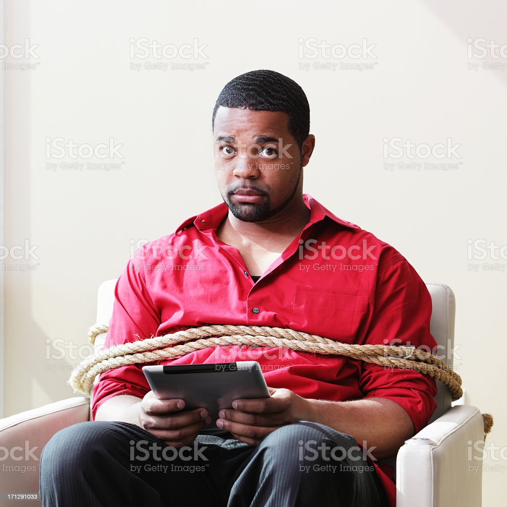 Hombre con ordenador vinculados con silla - foto de stock