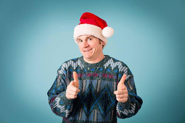 man with confident look wearing santa hat and ugly sweater - ugly sweater stock photos and pictures