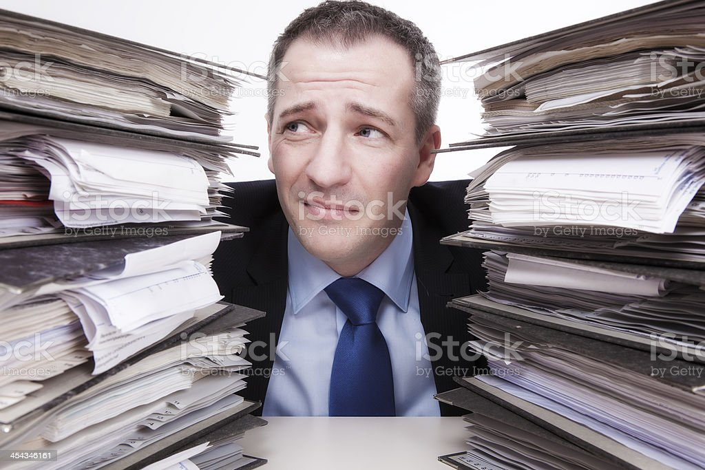 Man with confused expression between stacks of ring binders royalty-free stock photo
