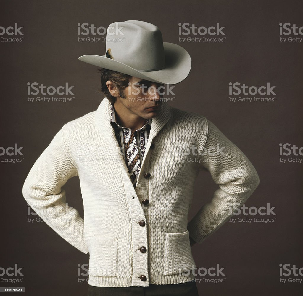 Man with cowboy hat against brown background stock photo