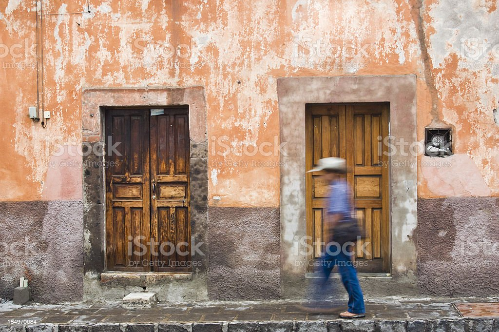 Man with cowboy hat in front of old wooden doors stock photo