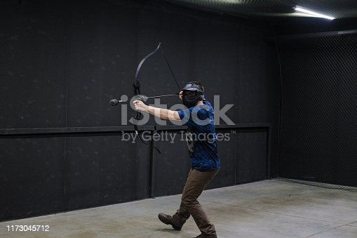 902406974 istock photo Man with crossbow arrows bow. The Archer takes aim, sharpshooter. Crossbow club. 1173045712