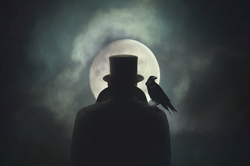 istock Man with crow on his shoulder observing the moon 862431166