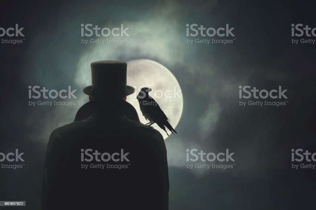 Man with crow on his shoulder observing the moon stock photo