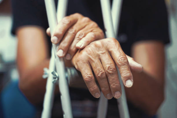 Man with crutch. Close-up. Side view Hands of old man on crutches. Close-up a elderly man with crutches. only senior men stock pictures, royalty-free photos & images