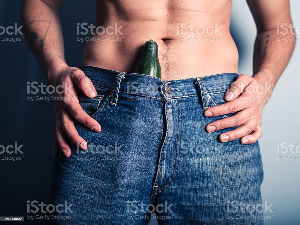 Man with cucumber down his pants stock photo