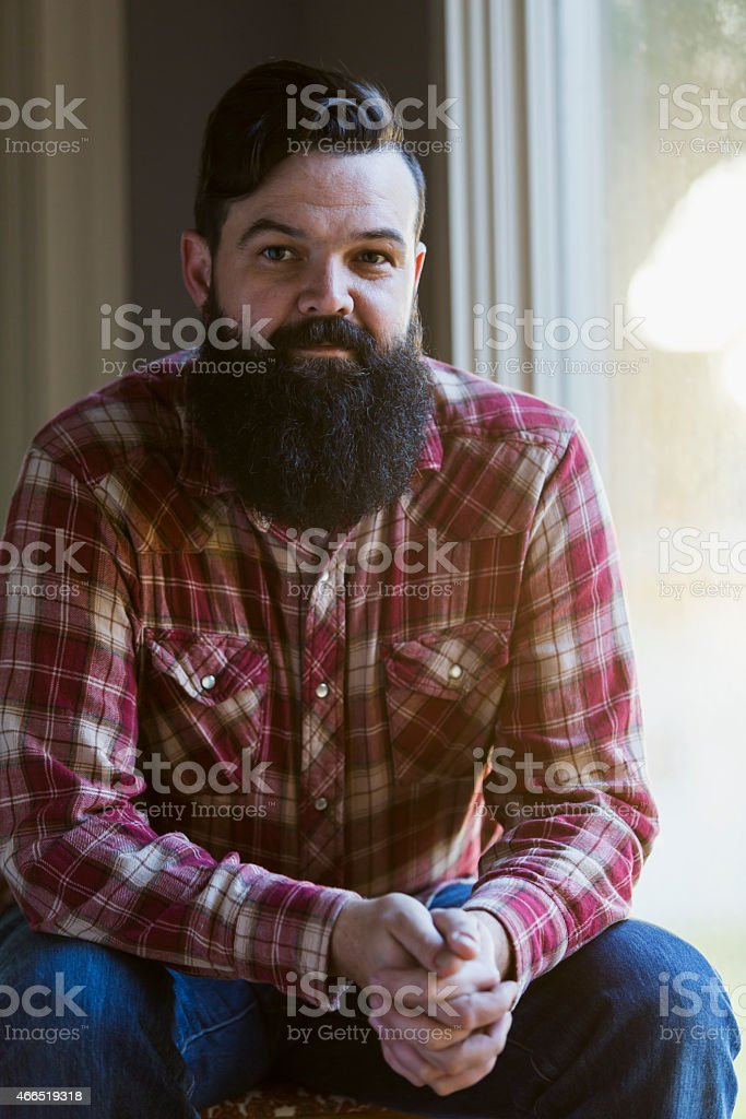 Man with dark beard, wearing plaid shirt and jeans stock photo