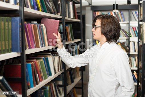 500129038istockphoto man with dark hair choosing a book 499127352
