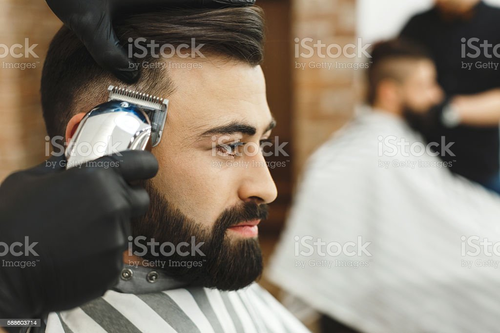Man with dark hair doing a haircut stock photo