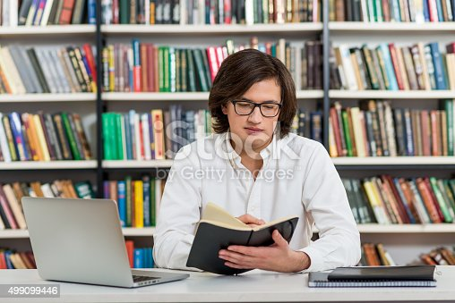 500129038istockphoto man with dark hair sitting at desk in library 499099446