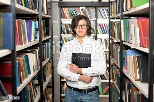 500129038istockphoto man with dark hair standing and holding a black book 499127858
