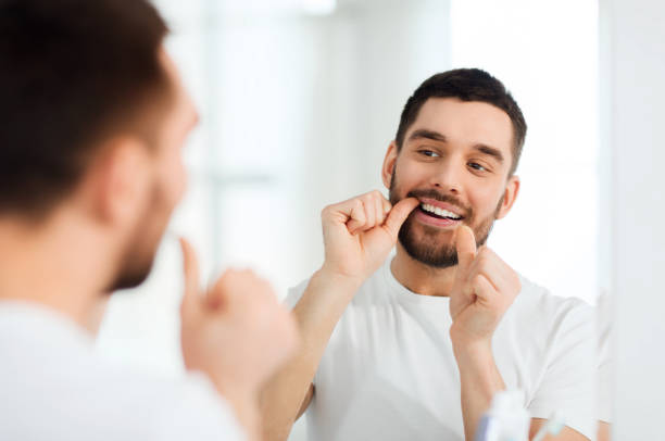 man with dental floss cleaning teeth at bathroom stock photo