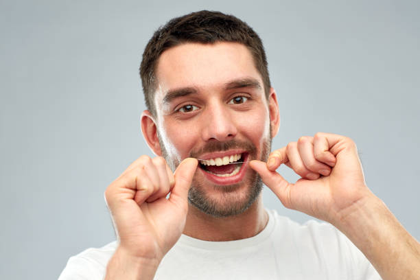 man with dental floss cleaning teeth over gray stock photo
