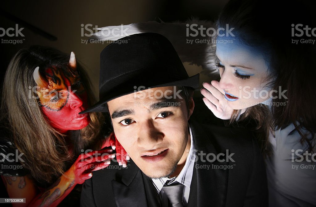 Man With Devil And Angel Telling Him What To Do Stock Photo