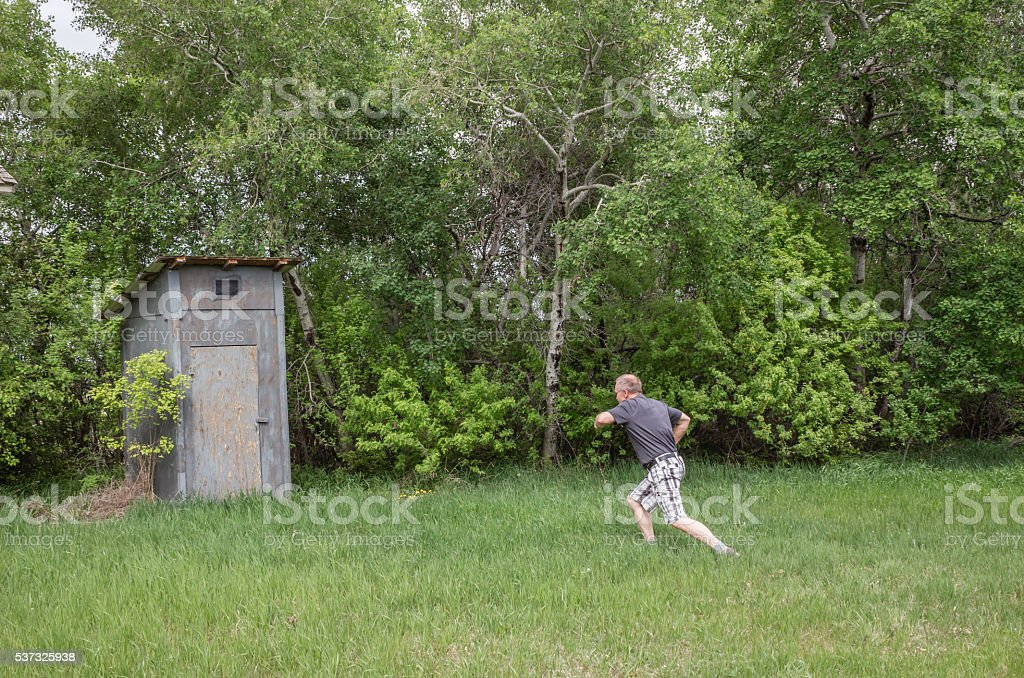 man with diarrhea running to the outdoor toilet. stock photo
