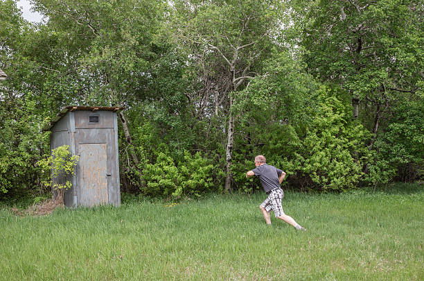 man with diarrhea running to the outdoor toilet. - diarrhea stock pictures, royalty-free photos & images