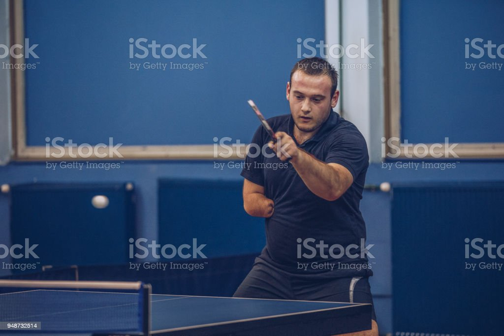Man with differing abilities playing table tennis stock photo