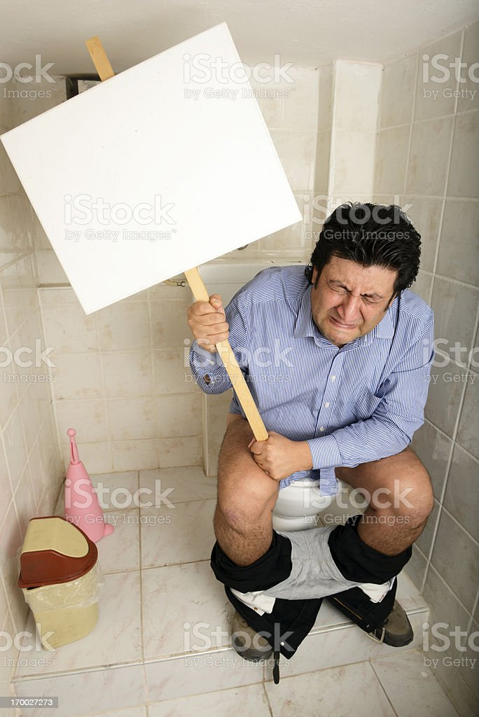 Man with digestive system problems on toilet holding sign stock photo