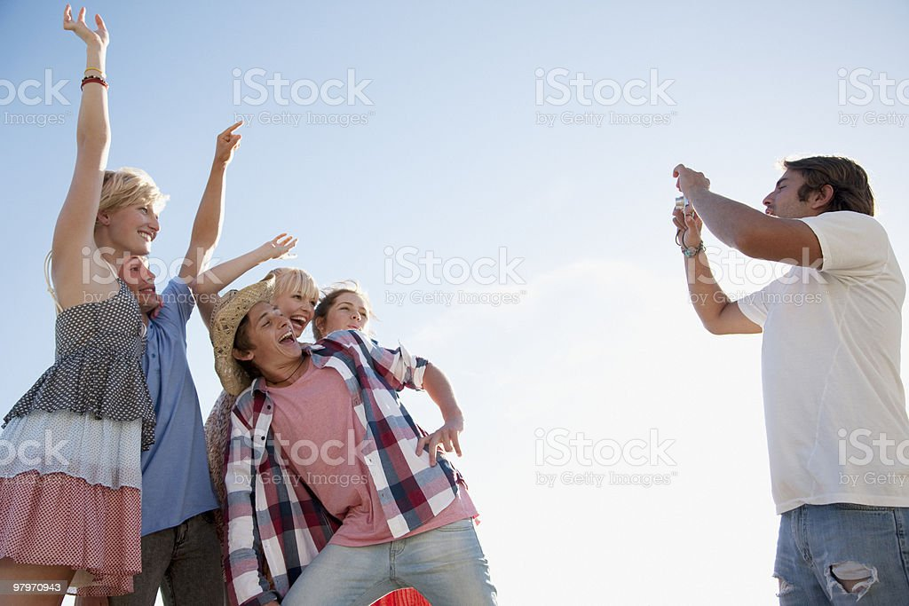 Man with digital camera taking photograph of friends royalty-free stock photo