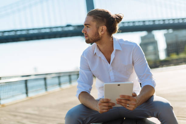 Man with digital tablet device Outdoors man bun stock pictures, royalty-free photos & images
