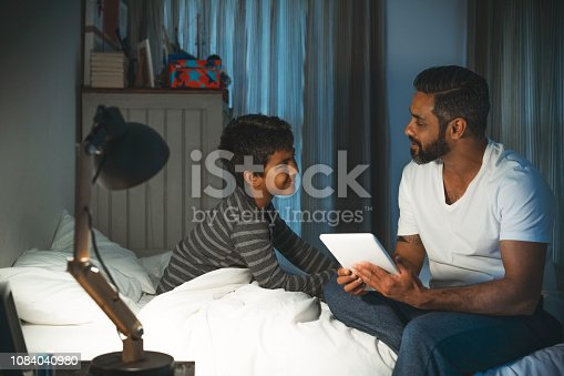 Smiling boy looking at father sitting on bed. Man is holding digital tablet with son in bedroom. They are at home.