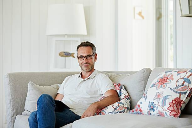 man with digital tablet sitting on sofa - lässiges wohnzimmer stock-fotos und bilder