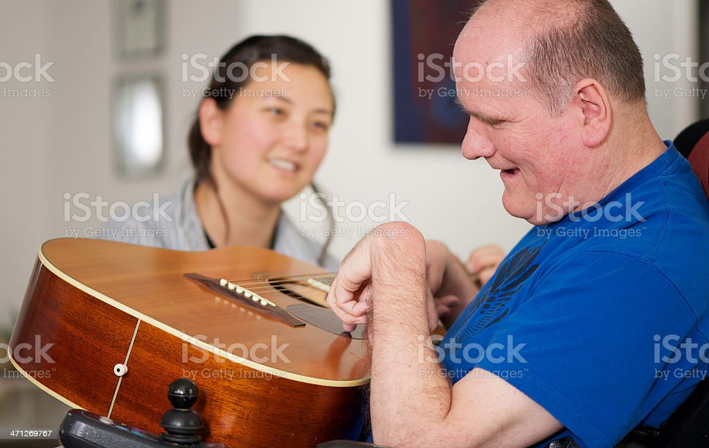 Man with disabiity, guitar, and a young woman stock photo