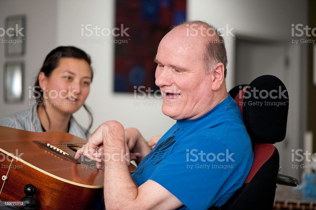 Man with disability playing guitar and woman looking on stock photo