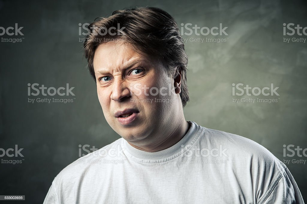 Man with disgusted expression over dark grey stock photo