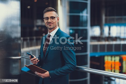 Attractive, adult man in chic formal wear standing inside business center. He looking at camera and holding telephone with document in hands