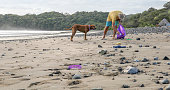 istock Man with dog picks up garbage on beach in the morning 1293786769