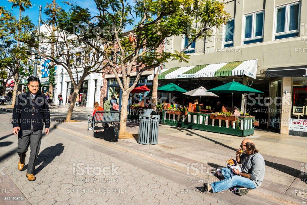 Man with dog snacking on Third Street Promenade, Santa Monica, USA stock photo