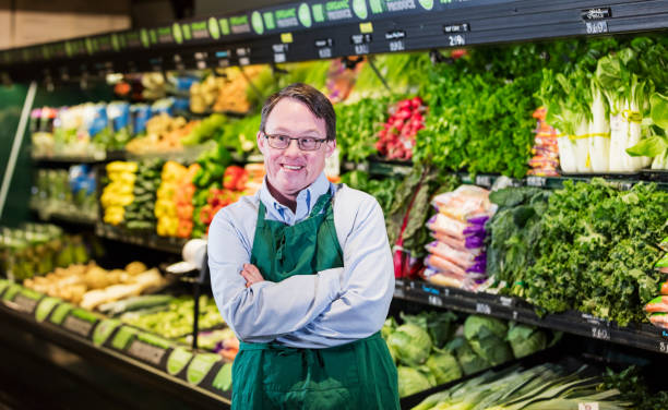 Man with down syndrome working in supermarket stock photo
