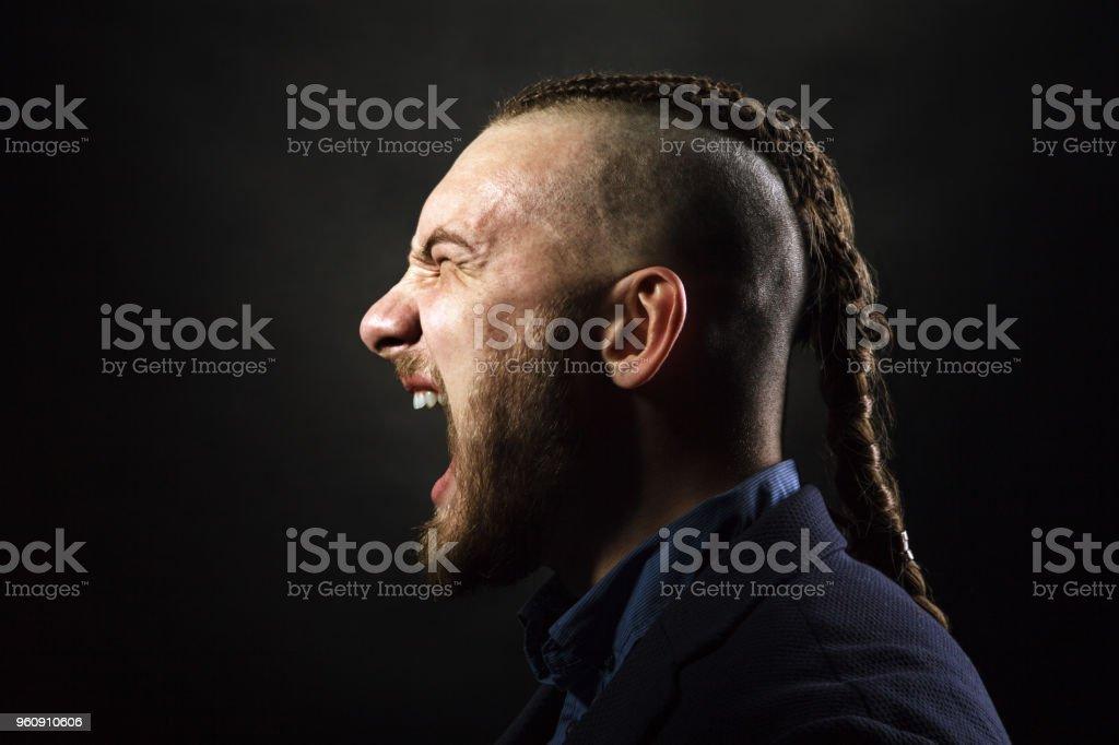 Mann mit Dreadlocks schreit vor Wut, sieht aus wie ein Wikinger, Irokesen Haarschnitt - Lizenzfrei Alternativer Lebensstil Stock-Foto