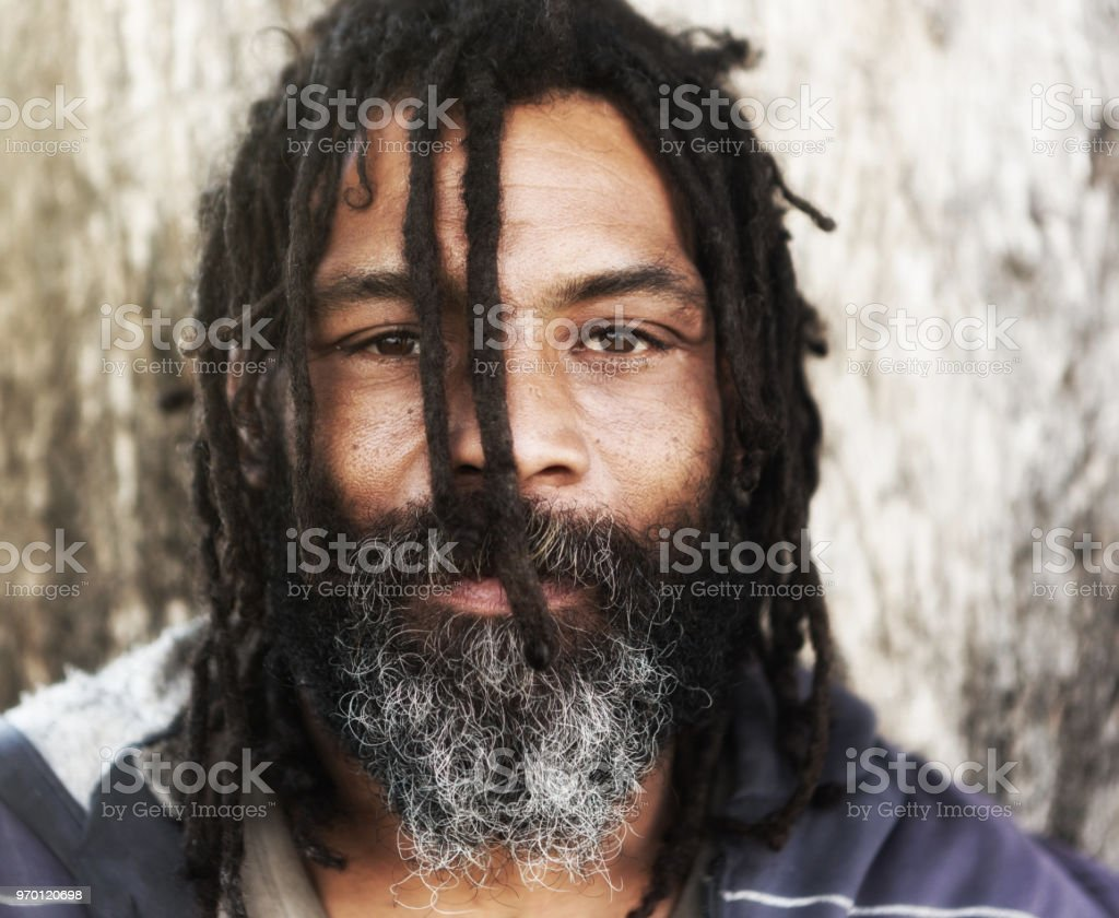 Man with dreadlocks stares intently at you stock photo
