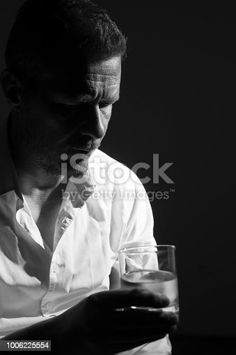 Drunk mid adult man holding glass of alcohol drink in his hand in low light room at night. Photo is taken with full frame dslr camera at night. Black and white photo.