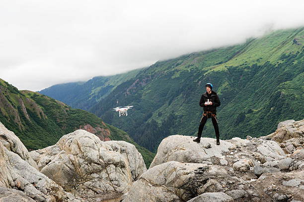 man with drone at glacier - flugdrohne stock-fotos und bilder