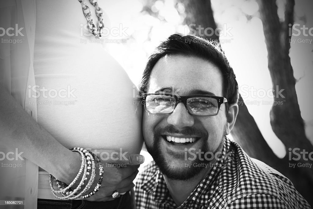 Man with Ear against Pregnant Belly royalty-free stock photo