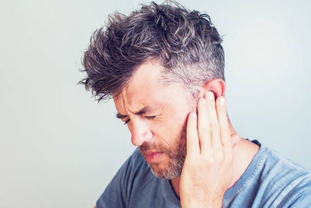 man with earache is holding his aching ear body pain concept - ear stock photos and pictures