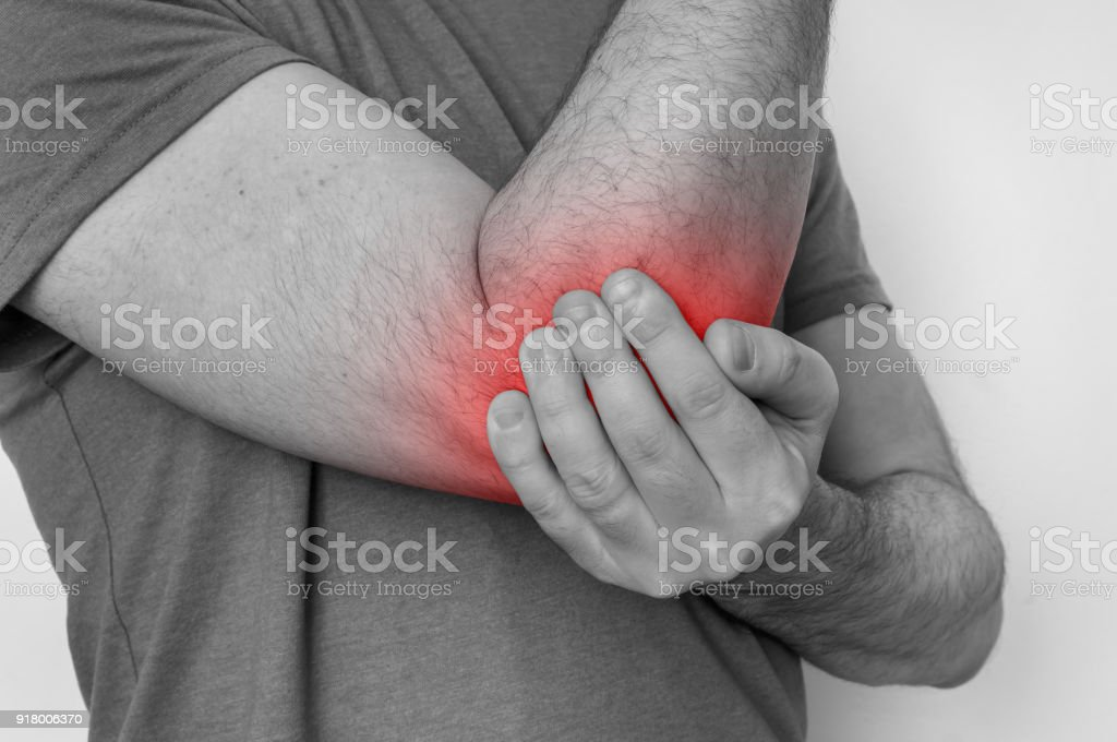 Man with elbow pain is holding his aching arm stock photo