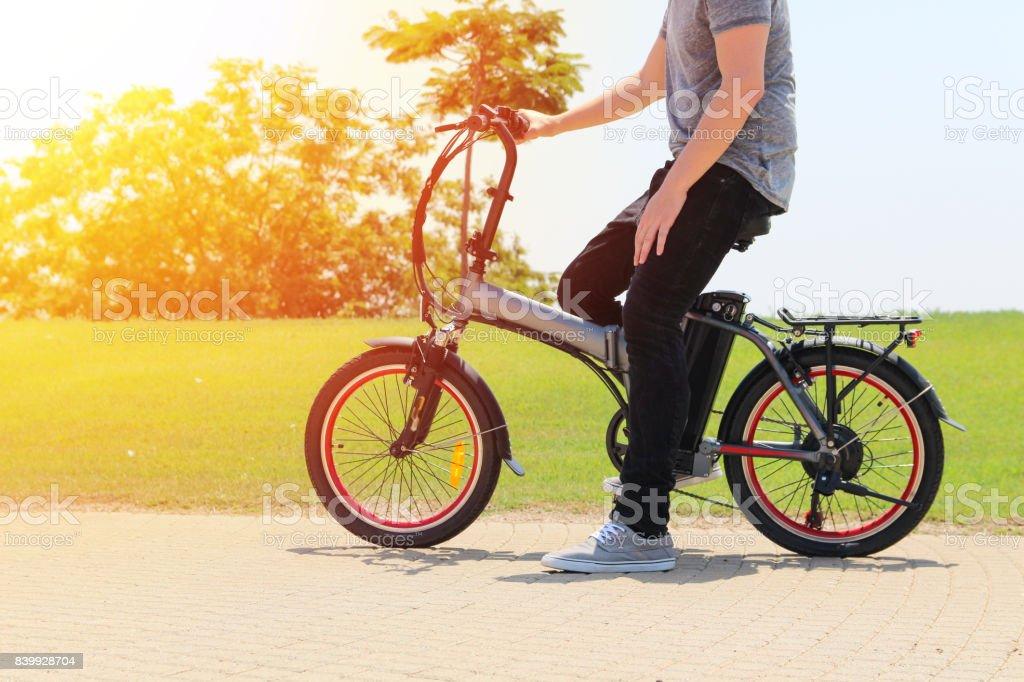 Un hombre con la bicicleta eléctrica en un parque - foto de stock